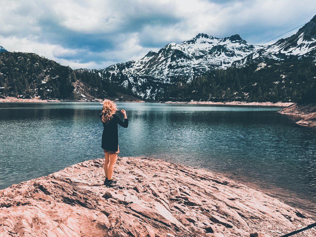 Ragazza in posa davanti al lago marcio incorniciato dalle montagne