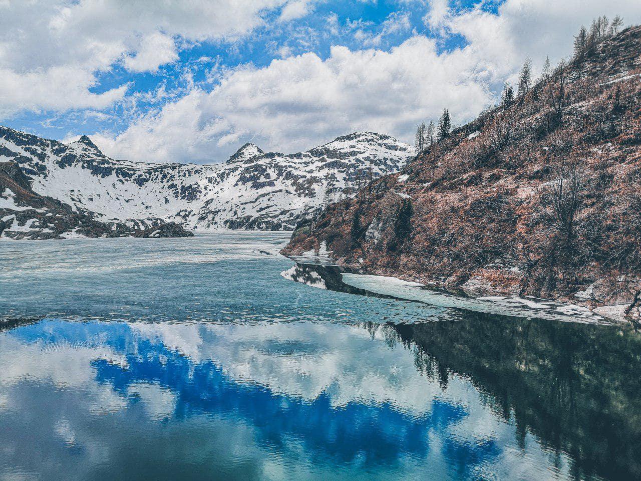 i laghi gemelli ancora ghiacciati avvolti dalle montagne innevate