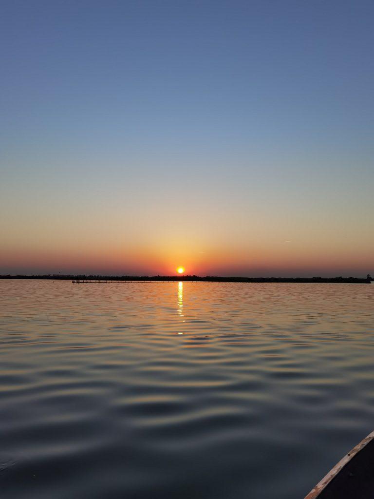 Le valli di comacchio al tramonto con il sole che scende e le sfumature blu e arancioni