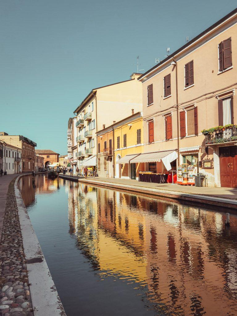Una delle vie di Comacchio con il canale al centro e i negozi al lato