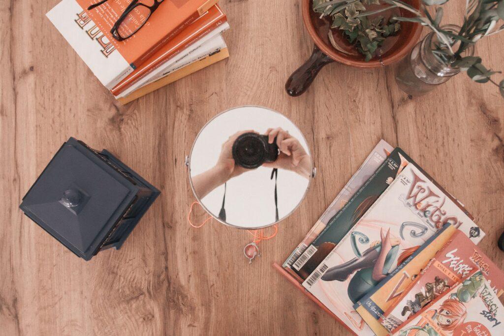 Come fare collaborazioni sui social flatlay dall'alto tavolo con libri riviste e specchio